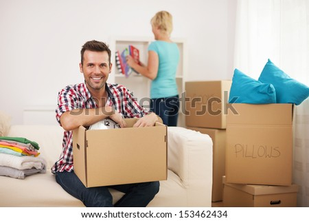 Young couple unpacking in their new home  - stock photo
