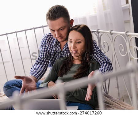 Young couple using a laptop lying on their bed, at home - stock photo