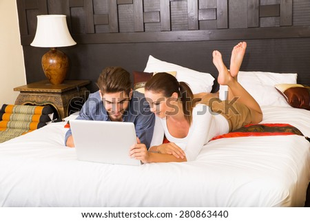 Young couple using a notebook in a asian hotel room while lying on the bed.  - stock photo