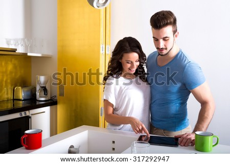 Young couple using a Tablet PC in the kitchen at home.