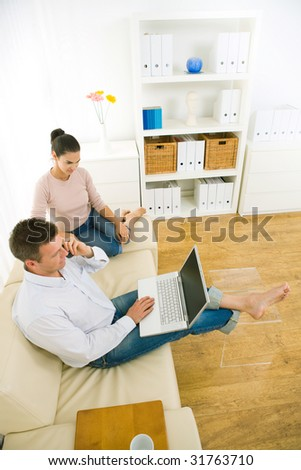 Young couple using laptop computer at home, sitting on couch. Man talkin on mobile phone. High-angle shot.