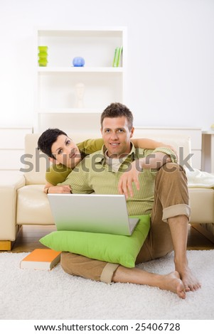 Young couple using laptop computer at home, sitting on floor and lying on couch, embracing. - stock photo