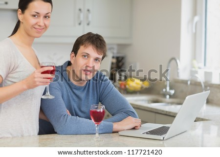 Young couple using laptop drinking red wine in kitchen - stock photo