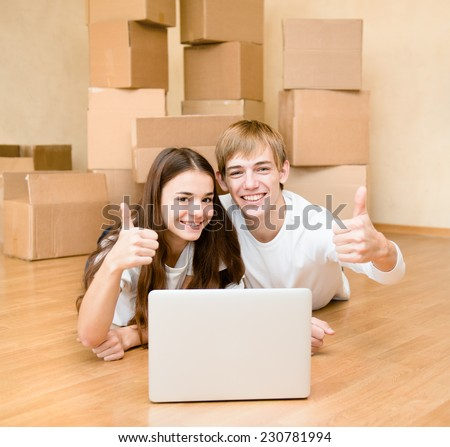 young couple using laptop in their new home and showing thumbs up - stock photo