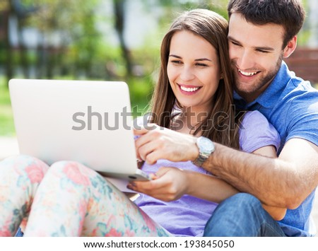Young couple using laptop outdoors  - stock photo