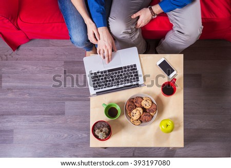 Young couple using laptop while sitting on couch - stock photo