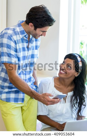 Young couple using mobile phone laptop at home