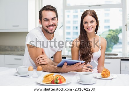 Young couple using tablet at breakfast at home in the kitchen - stock photo