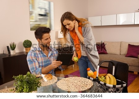 Young couple using tablet computer at home, eating apple. - stock photo