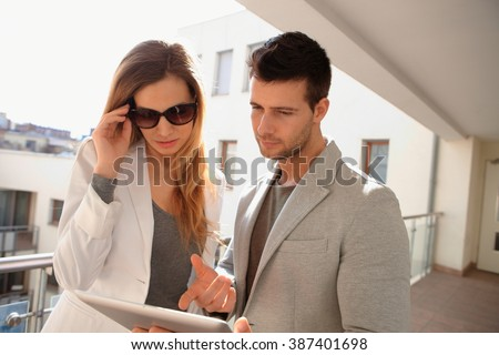 Young couple using tablet computer in corridor of apartment house. - stock photo