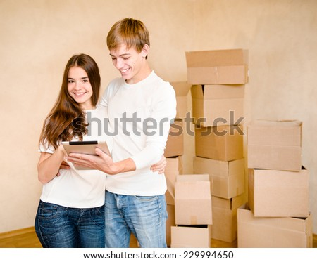 young couple using tablet computer in their new home - stock photo