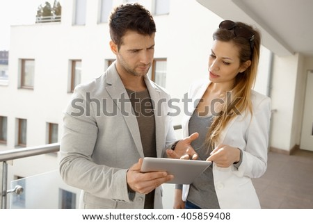 Young couple using tablet computer, talking.