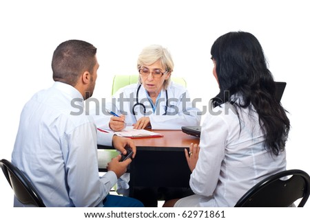 Young couple visiting senior doctor woman in office and having conversation isolated on white background - stock photo