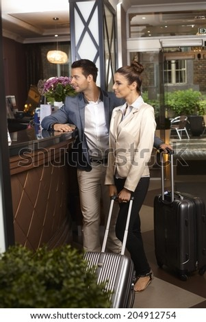 Young couple waiting at hotel reception upon arrival. - stock photo