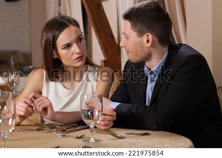 Young couple waiting for dinner in elegant restaurant - stock photo