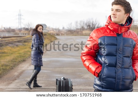 Young couple waiting with their suitcase in the middle of the road on a cold winter day with the young man keeping a sharp lookout for their transport while his girlfriend wanders around behind - stock photo
