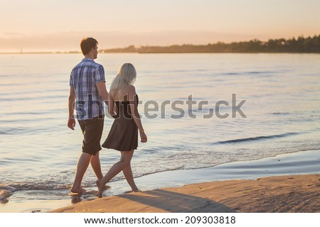 Young couple walk along the sea at sunset