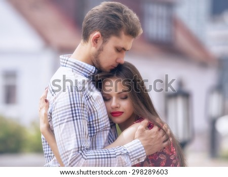 Young couple walk around the city, lovers of beautiful, cheerful. Brunette caucasian girl with long straight hair and bright lips and handsome guy hug each other, sunny, summer, outdoors.