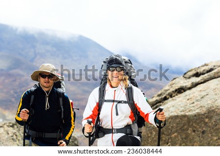 Young couple walking and hiking in Himalaya mountains in Nepal. Trekking in beautiful nature, climbing on high peaks, successful and motivation together, inspiration outdoors.