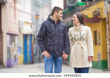Young Couple walking and holding hands - stock photo
