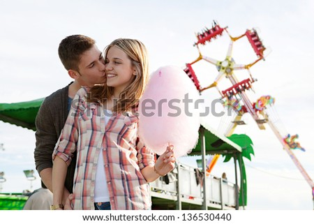 Young couple walking and kissing in an attractions park arcade with cotton candy floss and colorful rides in the background. - stock photo