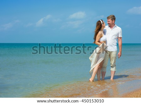 Young couple walking by the sea