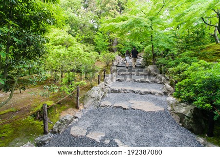 Young couple walking in a Japanese garden in Kyoto. Japan.