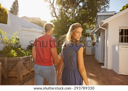 Young couple walking in the backyard holding hand in hand on a bright summer day, with woman looking back over shoulder at camera. - stock photo