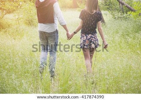 young couple walking in the park and holding hands - stock photo