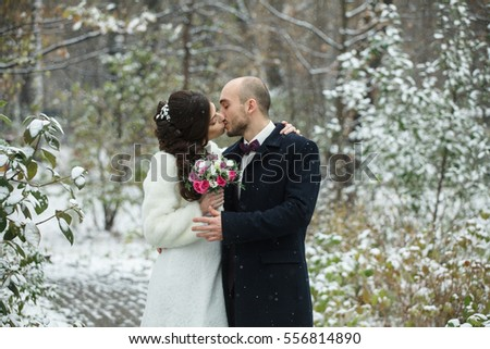 Young couple walking in winter park outdoors