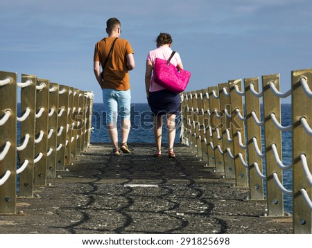 Young couple walking on a ocean pier - stock photo