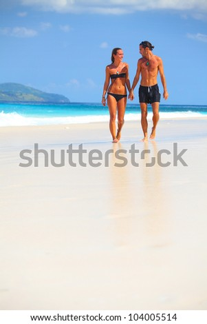 Young couple walking on a sandy beach along a coastline - stock photo