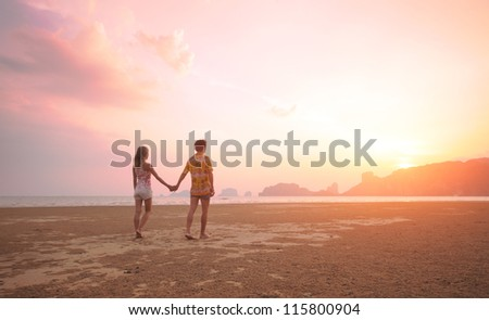 Young couple walking on a tropical beach at sunset. Pseudo HDR