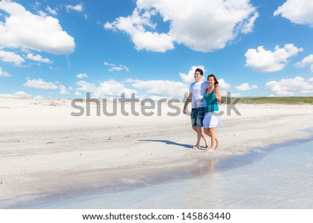 Young Couple Walking on Caribbean Beach - stock photo