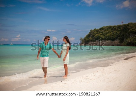Young couple walking on sandy beach near the sea