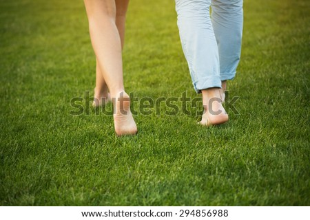 Young couple walking on the grass without shoes. Delicate feet of man and woman in beautiful nature. - stock photo