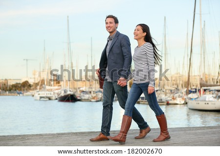 Young couple walking outdoors in old harbor, Port Vell in Barcelona Catalonia, Spain. Romantic happy woman and man holding hands enjoying life and romance outside. Multiracial Caucasian Asian couple. - stock photo