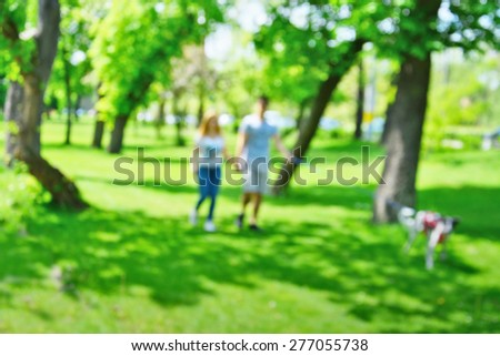 Young couple walking the dog in the park. Defocused park scene. - stock photo
