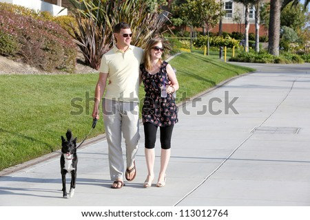 Young couple walking their dog - stock photo