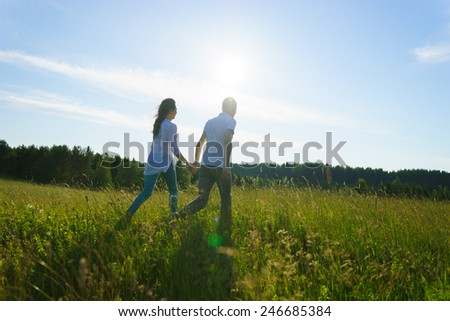 Young couple walking through green field - stock photo