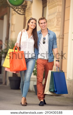 young couple walking with shopping bags - stock photo