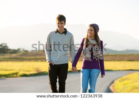 Young couple wandering along road in countryside. - stock photo