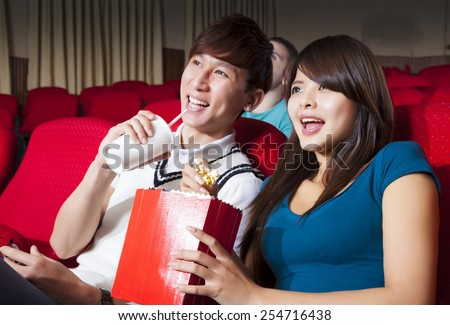 Young couple  watching a movie at the cinema - stock photo