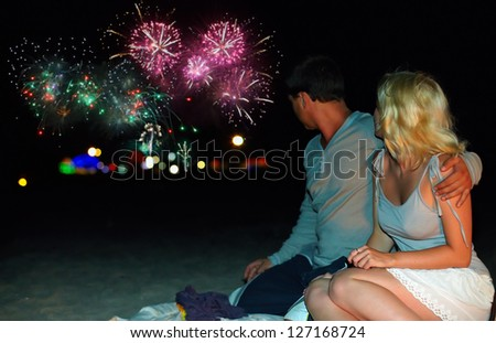 young couple watching colorful fireworks at the beach - stock photo
