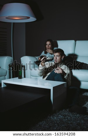 Young couple watching horror movie late at night - stock photo