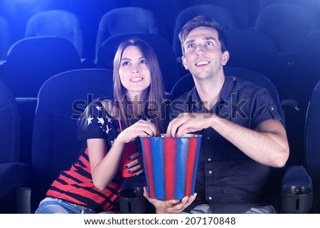 Young couple watching movie in cinema - stock photo