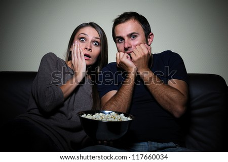 Young couple watching scary movie on tv - stock photo
