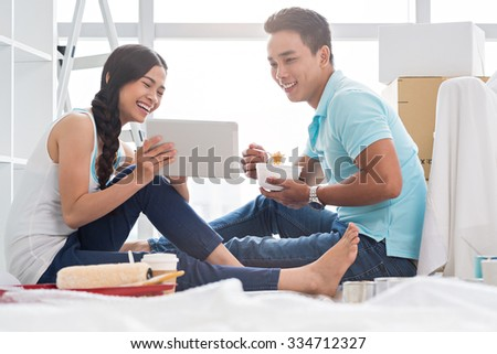 Young couple watching something funny on digital tablet when having lunch in new house
