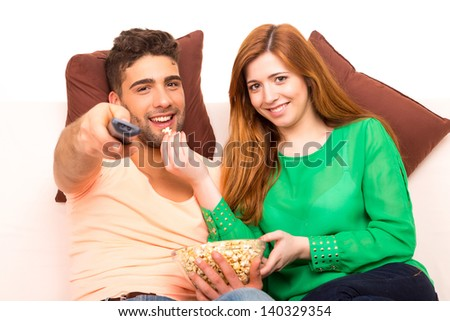 Young couple watching something on the television in the couch