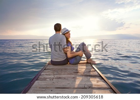 Young couple watching sunset - stock photo